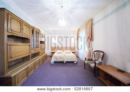 Light bedroom with a double bed, armchair and wall cabinet