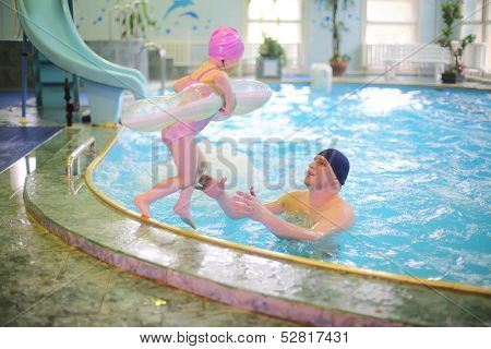 Little girl jumping with an inflatable round tube in the pool, her father in pool catches her