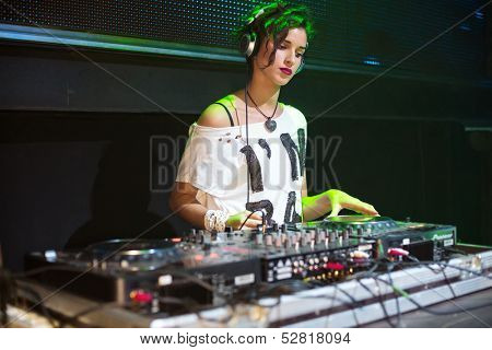 Young girl DJ with headphones standing behind the machine in nightclub