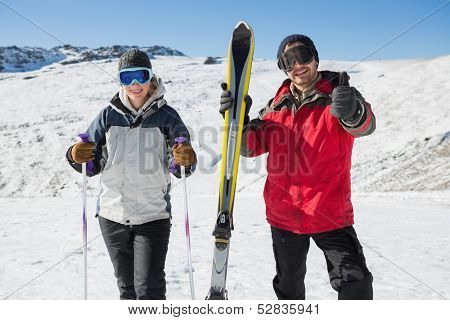 Portrait of a smiling couple with ski equipment standing on snow covered landscape