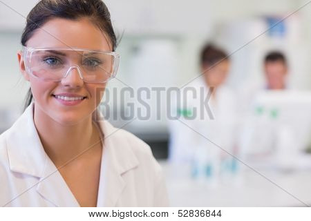 Close-up portrait of a female researcher with colleagues in the background at laboratory