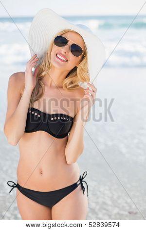 Attractive blonde in elegant black bikini smiling at camera on a beautiful sunny beach