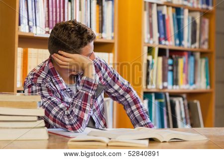 Handsome distracted student studying his books in library
