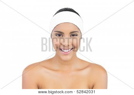 Smiling nude brunette with hairband looking at camera on white background