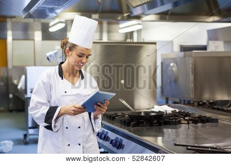 Young happy chef using tablet standing in professional kitchen