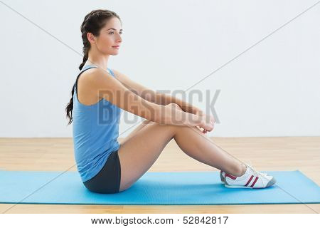 Full length profile shot of a fit young woman sitting upright on exercise mat