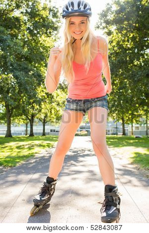 Casual cheerful blonde inline skating in a park