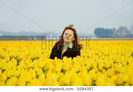 Beautiful Young Woman On The Field Of Yellow Tulips The Netherlands