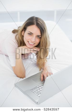 Gleeful woman using her notebook smiling cheerfully at camera lying on her bed