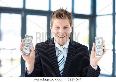 Smiling Businessman Holding Dollars