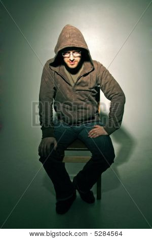 Attractive Man On Chair In Jacket With Hood
