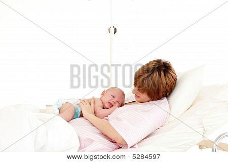 Patient Speaking To Her Newborn Baby In Bed