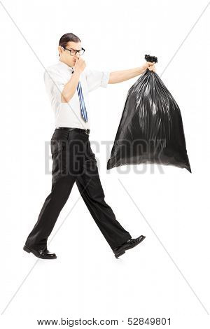 Full length portrait of a male closing his nose and carrying a stinky garbage bag isolated on white background