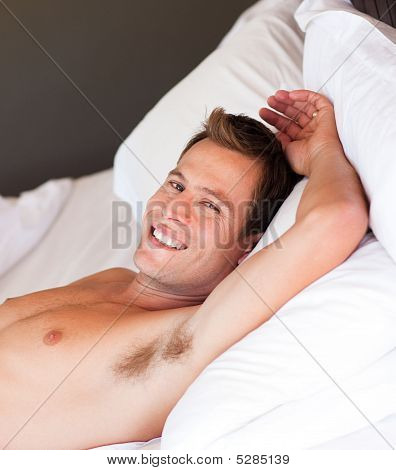 Smiling Young Man Relaxing In Bed