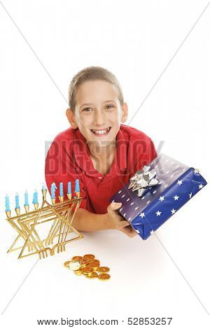 Cute Jewish boy with his Chanukah menorah, gift, and a dreidel and chocolate gelt coins.  White background.