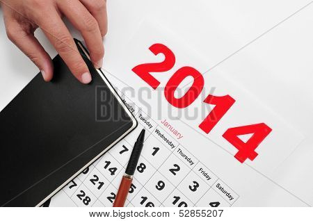 closeup of a desk with a notebook and a 2014 calendar
