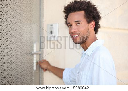 Man putting key in door