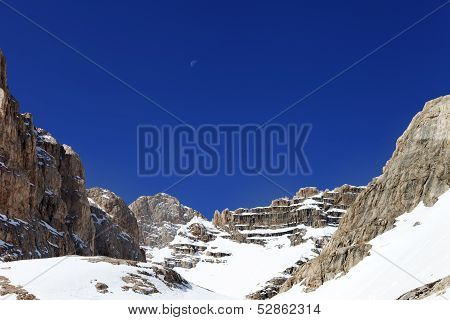 Snowy Rocks And Cloudless Blue Sky With Moon