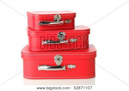 A set of matching luggage pieces stacked on top of each other. Three different sizes of red suitcase isolated on white with a slight reflection.