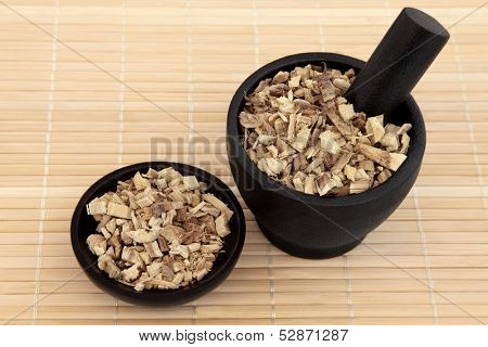 Licorice root used in chinese herbal medicine in a black stone mortar with pestle and bowl over bamboo. Gan cao. Glycyrrhiza glabra.