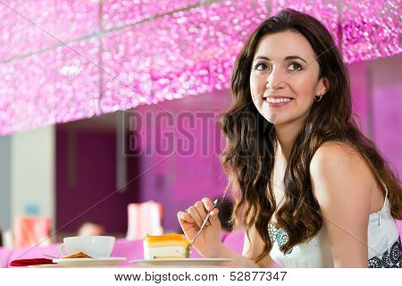 Young woman in a cafe or ice cream parlor eating a cake, maybe she is single or waiting for someone