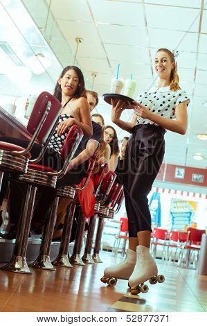 Friends or couples eating fast food and drinking milk shakes on bar in American fast food diner, the waitress serving with roller-skates