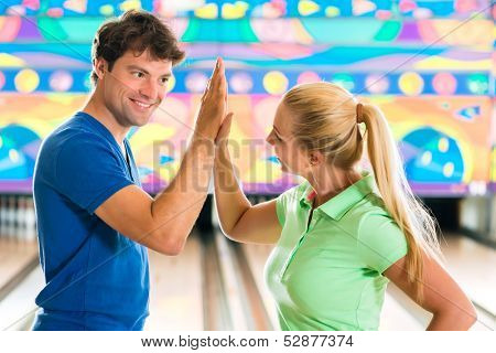 Young couple or friends, man and woman, playing bowling in front of the ten pin alley, they are a team