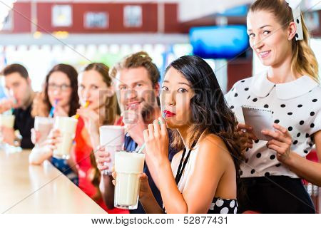 Friends or couples eating fast food and drinking milk shakes on bar in American fast food diner, the waitress is taking orders
