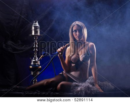 Young sexy woman in luxury underwear smoking the hookah in vintage interior