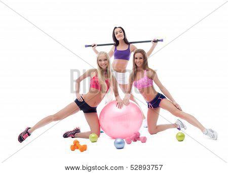 Cheerful pretty sportswomen posing in studio