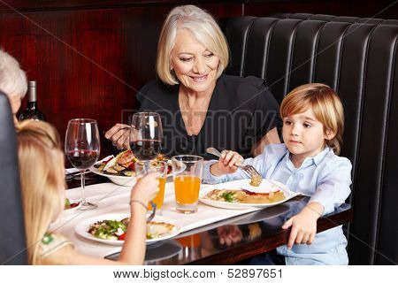 Smiling grandparents eating out with their grandchildren in a restaurant