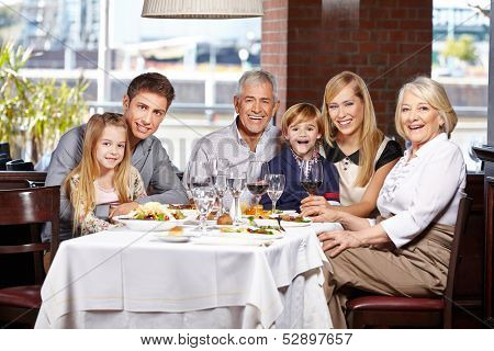 Happy family with children and seniors eating out in a restaurant