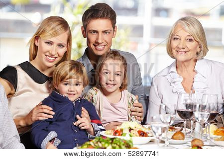Happy family with children and grandmother sitting at lunch table