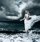 foto of tunic  - Woman in Splashing Dress Walking on Stormy Sea - JPG