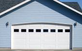 stock photo of garage  - Arched garage door opening on new residence brightly lit up by the warm summer sun - JPG