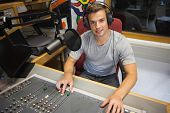 Handsome cheerful radio host moderating sitting in studio at college