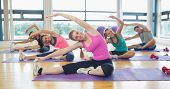 stock photo of stretching exercises  - Class and instructor doing stretching pilate exercises in fitness studio - JPG