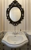 stock photo of oval  - Elegant white sink and oval mirror in toilet - JPG