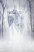 stock photo of cherubim  - Angelic male figure carrying a cross materialising in an atmospheric misty forest rendered in soft lilac tones - JPG