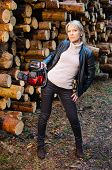 stock photo of chainsaw  - Young pretty woman with huge red chainsaw in the forestry - JPG