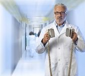 stock photo of defibrillator  - a doctor using a defibrillator with out of focus background - JPG