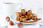 stock photo of toffee  - Many toffee on plate and cup of tea on napkin on wooden table - JPG