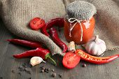 stock photo of sackcloth  - Composition with salsa sauce in glass jar - JPG