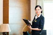 stock photo of housekeeper  - Asian Chinese Housekeeping manager or assistant controlling or checking the room or suit of a hotel with a checklist on tidiness - JPG