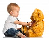stock photo of bear  - baby plays in doctor toy bear and stethoscope - JPG