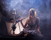 picture of opium  - Young sexy woman in luxury underwear smoking the hookah in vintage interior - JPG