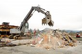 picture of track-hoe  - Large clamshell bucketed track hoe tearing down a former restaurant - JPG