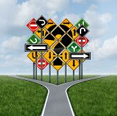picture of crossroads  - Confusing direction decision questions deciding on a clear strategy for solutions in business with a crossroads path to success choosing the right strategic plan with the challenge of a group of confusing traffic signs as a guide - JPG