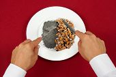 stock photo of smoker  - Man dining with Cigarette butts or fags and ash in a plate - JPG