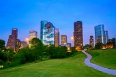 stock photo of nightfall  - Houston Texas modern skyline at sunset twilight from park lawn - JPG